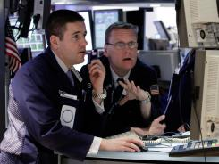 A pair of specialists work at their post on the floor of the New York Stock Exchange in late February 2012.