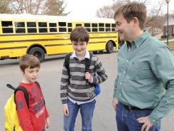 David Young greets his two sons Mark Young, 9, left, and Arthur Young, 12, as the boys return home from school in Vienna, Va. The Young family relocated last year from Madrid, Spain, and are saving to send the boys to college.