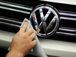 A Volkswagen worker polishes the badge on a car coming off the assembly line for VW Tiguan and Touran models in Wolfsburg, Germany.