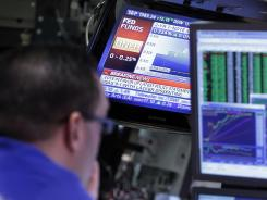 A television screen at a post on the trading floor of the New York Stock Exchange shows the decision of the Federal Reserve to keep rates unchanged on March 13, 2012.