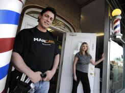 Joel and Lisa Martin pose outside their barber shop and salon in Rosemount, Minn.