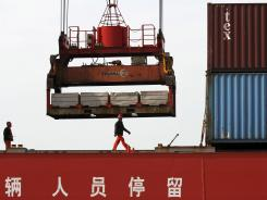 A worker walks past a crane at a container port in Jinjiang in southeast China's Fujian province on March 10, 2012.