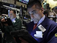 Trader Vincent Quinones, right, works on the floor of the New York Stock Exchange on March 13, 2012.