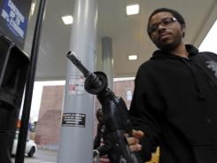 Michael Morris replaces the nozzle after putting gas in his car, in Philadelphia on Feb. 24, 2012. A sharp jump in gas prices drove a measure of U.S. consumer costs up in February. But outside higher pump prices, inflation stayed mild.