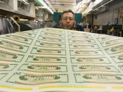 Jose R. Del Toral inspects stacks of freshly made 20-dollar bills at the Bureau of Engraving and Printing in Washington, D.C.