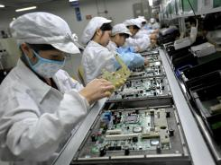 Workers assemble electronic components in 2010 at a Foxconn plant in Shenzhen, in China's southern Guangzhou province.