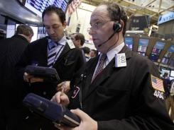 Gordon Charlop, right, works with fellow traders on the floor of the New York Stock Exchange on March 13, 2012.