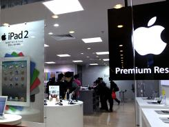 Customers view Apple products at Tee Mall on in Guangzhou, China.
