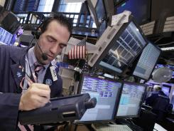 Trader Gregory Rowe works on the floor of the New York Stock Exchange Monday, March 19, 2012.