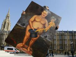 Political painter Kaya Mar carries his painting depicting Britain's Chancellor of the Exchequer, George Osborne, through Westminster in London, Wednesday, March 21, 2012.