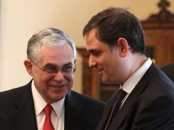 Greek Prime Minister Lucas Papademos, left, speaks with the new Greek Finance Minister Philippos Sachinidis during the swearing in ceremony at the Presidential Palace in Athens, Wednesday, March 21, 2012.
