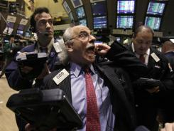 Trader Peter Tuchman, center, works on the floor of the New York Stock Exchange on March 13, 2012.