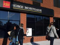 People walk by a Wells Fargo Home Mortgage branch in Brooklyn, N.Y. , in this December 2008 file photo.