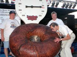 In this July 24, 1998 photo, Murray Lender kisses the world's largest bagel while baker Larry Wilkerson, left, and Lender's Bagel Bakery manager Jim Cudahy watch.