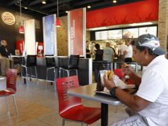 Norman Garcia eats a burger and fries at a Burger King restaurant in Miami. Burger King is retooling the look of its restaurants and adding 10 new menu items.