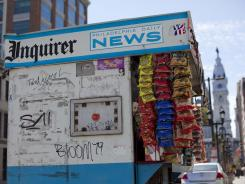 "A newsstand displays the logos of ""The Philadelphia Inquirer"" and ""Daily News"" in view of Philadelphia's City Hall."