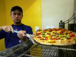 West Lopez takes a chicken pineapple pizza from the oven at Domino's Pizza in Farmington Hills, Mich., Dec. 2, 2010.