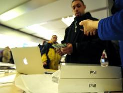 A customer buys Apple's new iPad at Apple's flagship store on Fifth Avenue, in New York, on March 16, 2012.