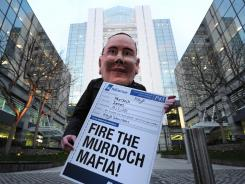 A demonstrator wearing a mask representing James Murdoch outside News International offices in London Feb. 29, 2012.
