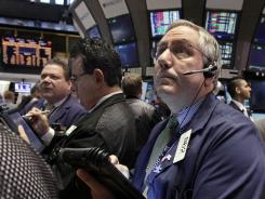 Trader Warren Meyers, right, works on the floor of the New York Stock Exchange Monday, April 2, 2012.
