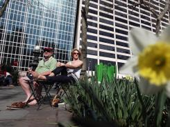 A couple sits in the sun in New York's Bryant Park during warm afternoon weather on March 14.
