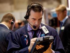 A trader works on the floor of the New York Stock Exchange March 26, 2012.
