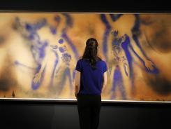 "A woman looks at ""FC 1"" (Light Color 1) by French painter Yves Klein, in Paris on April 5, 2012."