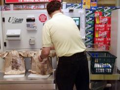 A customer bags items at the self check-out at a Harris Teeter grocery store.