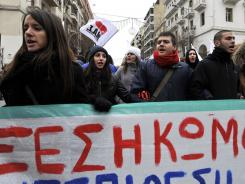 Protesters carry a banner during a protest in the northern port city of Thessaloniki, Greece, on Saturday, Feb. 11, 2012.