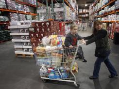 Tina VanPelt and her son Soloman, 4, shop at a Costco wholesale store, in, Portland, Ore., in late 2011. Wholesale businesses increased their stockpiles in February, the government says.