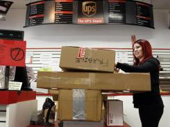 UPS Store employee, Candy Mojica, weighs packages before shipping at The UPS Store in the Lake Balboa area of Los Angeles, in January 2012.