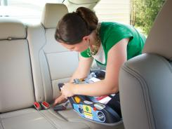 Whitney Amyett struggles to install a rear-facing infant seat.