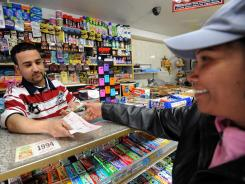 Clerk Abdulwali Mohamed Osaim, left, sells lottery tickets at a convenience store on the east side of Manhattan on March 30, 2012 in New York.