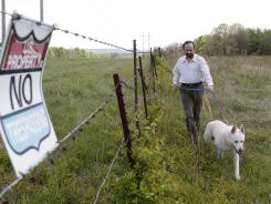 Geoffrey Sea, owner of 88 acres adjacent to the USEC project, walks next to the fence that separates his property from the USEC property on Friday with his dog Mweowa.