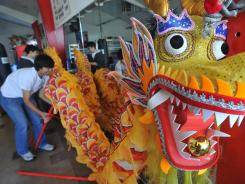 The head of a crafted dragon imported from China is displayed for a group of teens in Fresno, Calif., on Feb. 26.
