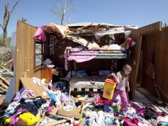 Sarah Gunter, 6, sifts through her tornado-destroyed home at Pinaire Mobile Home Park in Wichita on April 16.