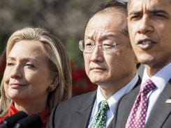 Jim Yong Kim is flanked by President Obama and Secretary of State Hillary Clinton at a March 23 White House appearance.