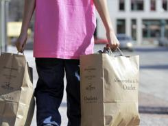 A shopper carries bags of merchandise in Freeport, Maine, in March.