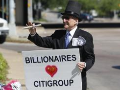 Grant Youngman wears a costume and holds a sign during an Occupy Dallas tax day protest outside the Citigroup shareholders meeting Tuesday, April 17, 2012, in Dallas.