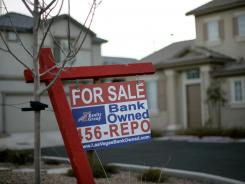 A for-sale sign stands in front of a bank-owned home in Las Vegas (file photo).