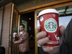A customer holds a coffee drink in front of a Starbucks coffee shop at the company's corporate headquarters in Seattle as another patron walks out the door.