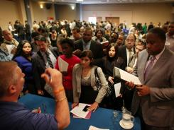Job seekers line up to give their resumes to a representivie of an employment agency at a job fair at a Holiday Inn on April 18, 2012 in New York City.