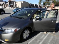 Heather Peters stands next to her car Jan. 3 as she talks with reporters outside small claims court in Torrrance, Calif.