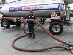 A tanker truck delivers gasoline at a service station in Los Angeles.
