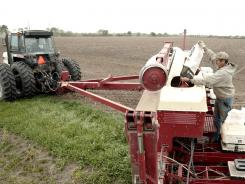Greg Magsmen fills his planter with seed corn as near White Heath, Ill., April 13, 2012.