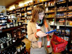 Paige Worthy uses her iPad to check a recipe while shopping on March 3 at Gene's Sausage Shop & Delicatessen in Chicago.