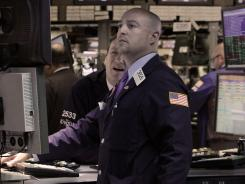 Stock trading specialists Patrick King, left, and Frank Babino work on the floor of the New York Stock Exchange on April 16, 2012.
