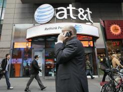 A man using a cell phone passes an AT&T store in New York in this file photo.