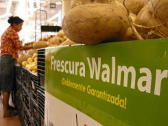 A woman shops in the produce aisle of a Wal-Mart store in Mexico City, Mexico. According to reports, Wal-Mart de Mexico orchestrated a campaign of bribery to win market dominance by paying bribes to obtain permits in parts of the country.