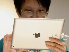 A visitor tries out a new iPad tablet computer at an Apple store in Klang, outside Kuala Lumpur, Malaysia.